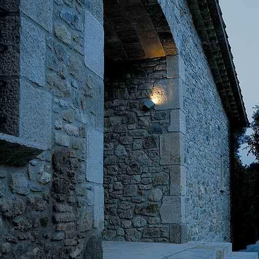 Kleine blendfreie Beton Wandleuchte außen an Steinfassade