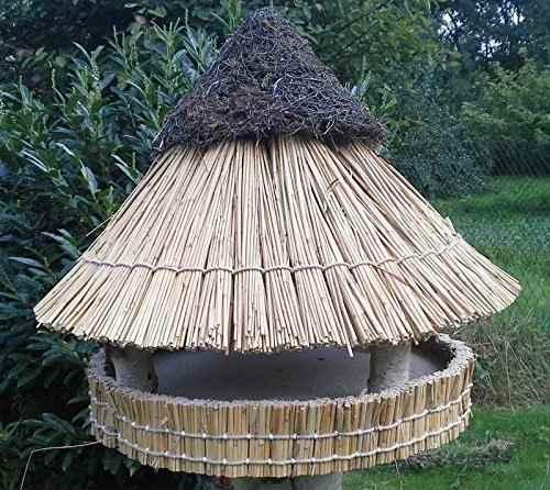 Vogel Futterhaus mit Reetdach stehend
