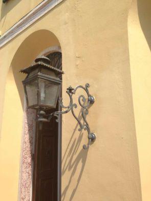 Alte Außenwandleuchte mit verschnörkeltem Wandhalter