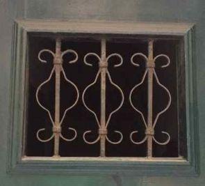 Altes kleines schmiedeeisernes Fenstergitter