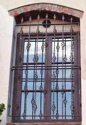 Aufwändiges altes Fenstergitter mit Pfeilen