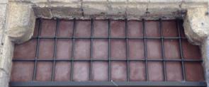 Altes Fenstergitter in alter Stadtmauer