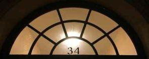 Halbrundes Fenstergitter vor Glas mit Hausnummer