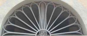 Halbrundes Fenstergitter verziert mit Monogramm