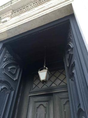 Historische Deckenleuchte hängend vor imposanten Eingang