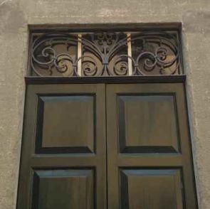 Altes verschnörkeltes Fenstergitter oberhalb der Haustür