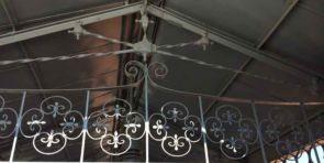 Verschnörkeltes Geländer unter einer Metalldachkonstruktion