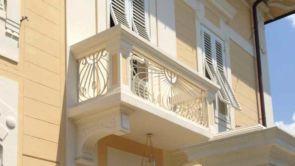 Weißer Balkon mit schönen Schmiedearbeiten
