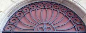 Geschmiedetes halbrundes Fenstergitter vor rotem Hintergrund